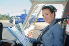 Woman holding map in helicopter cockpit Royalty Free Stock Images