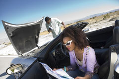 Woman Holding Map With Man Checking Car Engine Stock Images