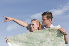 Woman holding map while man pointing away against sky Royalty Free Stock Images