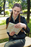 Woman holding a map in the park Stock Photos