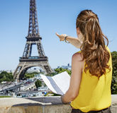 Woman holding map and pointing on Eiffel tower in Paris. Having fun time near the world famous landmark in Paris. Seen from behind young woman in bright blouse Royalty Free Stock Image