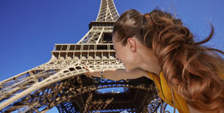 Woman holding map and pointing on Eiffel tower, Paris. Touristy, without doubt, but yet so fun. Seen from behind young woman holding map and pointing on Eiffel Royalty Free Stock Photography