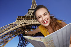 Woman holding map and pointing in front of Eiffel tower, Paris. Touristy, without doubt, but yet so fun. Portrait of smiling young woman holding map and pointing Stock Photo