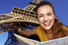 Woman holding map and pointing in front of Eiffel tower, Paris. Touristy, without doubt, but yet so fun. Portrait of smiling young woman holding map and pointing Stock Photography