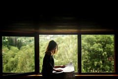 Woman holding map sitting at window with view at amazing mountai. Ns in wooden house, planning summer travel or architect concept, space for text Royalty Free Stock Photography