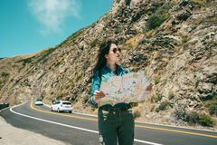 Woman holding map while standing on road. Woman holding a guide map to check while standing on the road surrounded by mountains and cliff royalty free stock image