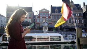 Woman holding map. Sunny day in Ghent. Woman walking in historic centre. Close-up pretty girl concentrate on map in hands at background blured building in stock footage