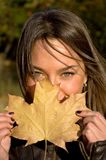 woman holding a maple leaf Royalty Free Stock Images
