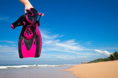 Woman holding mask and flippers for swimming on the background t Stock Photography