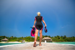 Woman holding mask and flippers for swimming on the background t. He beach Stock Photo