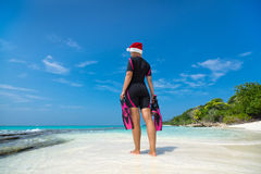 Woman holding mask and flippers for swimming in santa hat on the. Beach Stock Images