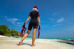 Woman holding mask and flippers for swimming in santa hat on the. Beach Stock Photos