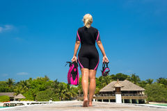 Woman holding mask and flippers for swimming on wooden pier.  Stock Image