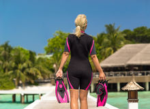 Woman holding mask and flippers for swimming on wooden pier Stock Images