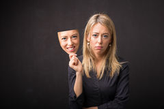 Woman holding mask of her happy face. Woman with sad face  holding mask of her happy face Royalty Free Stock Photos
