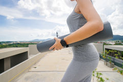 Woman holding mat. Yoga on the roof. Healthy lifestyle concept and technology. Young woman holding fitness mat with smartwatch on her hand Stock Image
