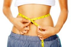 Woman holding measuring tape around waist Stock Photo