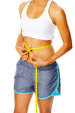 Woman holding measuring tape around waist Royalty Free Stock Photo