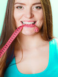 Woman holding measuring tape between teeth. Royalty Free Stock Images