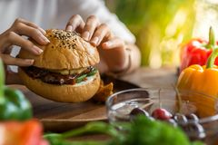 Woman holding meat burger in restaurant.. Royalty Free Stock Photography