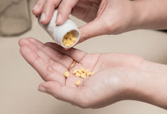 Woman holding medicines bottle and pouring some pills on another hand for treatment medication Royalty Free Stock Photo