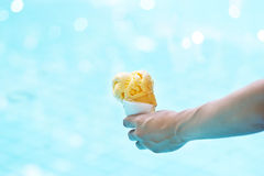Woman holding melting ice cream in waffles cone in hands on pool Royalty Free Stock Image