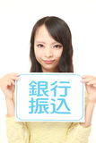 Woman holding a message board with the phrase BANK TRANSFER in KANJI Stock Photography