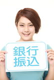 Woman holding a message board with the phrase BANK TRANSFER in KANJI Royalty Free Stock Images