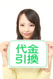 Woman holding a message board with the phrase CASH ON DELIVERY in KANJI Stock Photo