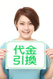 Woman holding a message board with the phrase CASH ON DELIVERY in KANJI Royalty Free Stock Photography