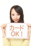 Woman holding a message board with the phrase CREDIT CARD ACCEPTED in Japanese Stock Images