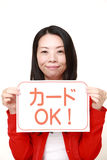 Woman holding a message board with the phrase CREDIT CARD ACCEPTED in Japanese Royalty Free Stock Photos