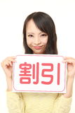 Woman holding a message board with the phrase DISCOUNT in KANJI Royalty Free Stock Photo