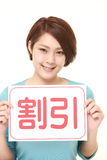 Woman holding a message board with the phrase DISCOUNT in KANJI Royalty Free Stock Images