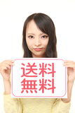 Woman holding a message board with the phrase FREE SHIPPING in KANJI Royalty Free Stock Photography