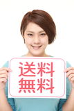 Woman holding a message board with the phrase FREE SHIPPING in KANJI Stock Photo