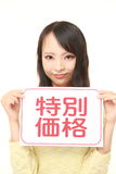 Woman holding a message board with the phrase SPECIAL OFFER in KANJI Royalty Free Stock Image