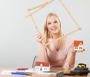Woman holding meter frame and small house. Young adult woman, architect holding a meter frame and exposing small house stock photos
