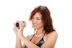 Woman holding a micro four thirds photo camera. Young beautiful smiling woman holding a micro four thirds photo camera. Isolated over white background stock images