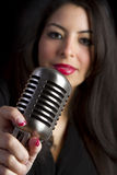Woman Holding Microphone. Retro woman holding elvis microphone stock photography