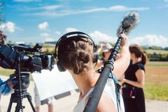 Woman holding microphone on a boom during video production. Capturing audio stock image