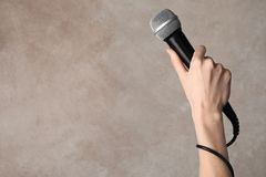Woman holding microphone on color background. Space for text royalty free stock photography