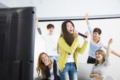 Woman holding microphone and singing at karaoke. Young women holding microphone and singing at karaoke royalty free stock photography