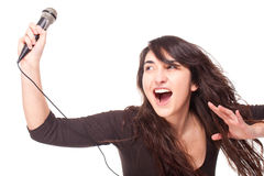Woman holding a microphone and singing loud Stock Photo