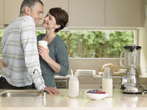 Woman Holding Milkshake While Looking At Husband In Kitchen Royalty Free Stock Image