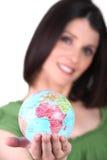 Woman holding a mini-globe Stock Photography