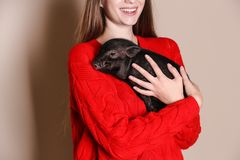Woman holding mini pig on color background. Closeup stock image