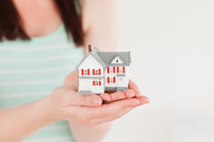 Woman holding a miniature house while standing Stock Photos