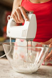 Woman holding mixer and making whipped cream in glass bowl Stock Photo