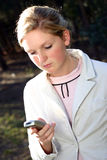 Woman holding mobile phone. Young woman holding mobile phone outdoors Royalty Free Stock Images